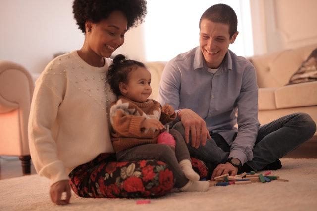 rodina, žena, muž, a dítě, sedí doma na zemi na koberci